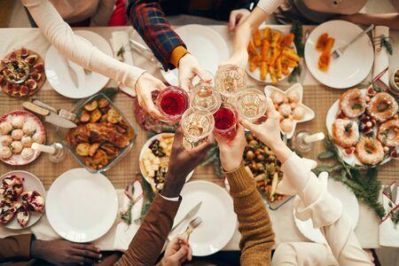 Draufsichthintergrund von Leuten, die Gläser über festlichem Esstisch heben, während sie Weihnachten mit Freunden und Familie feiern, Kopienraum Standard-Bild