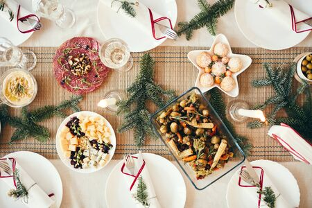 Top view background of cozy table setting decorated with fir branches for Christmas banquet focus on delicious homemade food, copy space Stock Photo
