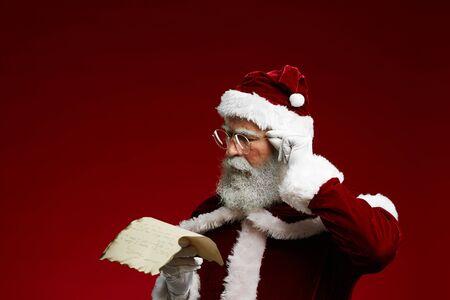 Portrait de la liste de lecture classique du Père Noël sur parchemin et ajustant les lunettes en se tenant debout sur fond rouge, espace pour copie Banque d'images