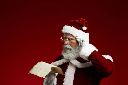 Portrait of classic Santa reading list on parchment and adjusting glasses while standing against red background, copy space