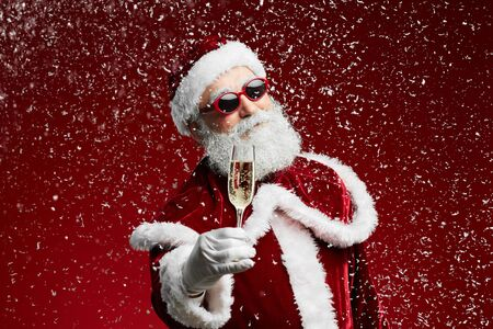 Waist up portrait of cool Santa holding champagne glass while standing over red background with snow falling, copy space