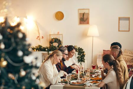 Wide angle view at modern young people celebrating Christmas sitting at dinner table in elegant dining room, copy space