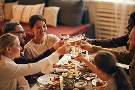 High angle view at elegant young people clinking champagne glasses while enjoying Christmas dinner at home, copy space