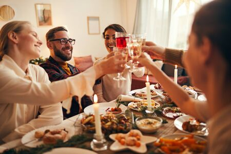 Side view portrait of elegant young people clinking champagne glasses while enjoying Christmas dinner at home 스톡 콘텐츠