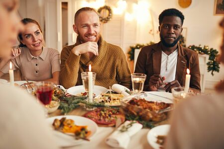 Poirtrait of multi-ethnic group of people enjoying dinner sitting at table with delicious food, focus on smiling bearded man in center 스톡 콘텐츠