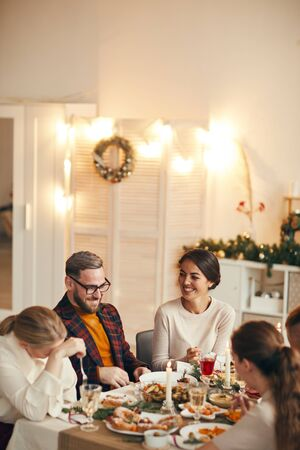 High angle view at successful adult couple laughing cheerfully while celebrating Christmas with friends at dinner table, copy space