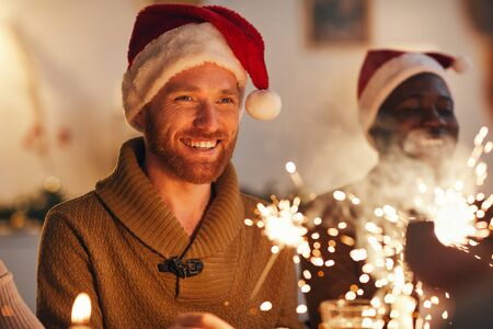 Portrait of cheerful bearded man wearing santa hat while enjoying Christmas celebration with friends and family