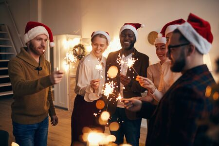 Multi-ethnic group of people holding sparkling lights while enjoying Christmas celebration with friends and family Stock Photo