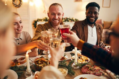 Multi-ethnic group of cheerful adult people clinking champagne glasses while enjoying Christmas dinner at home, copy space