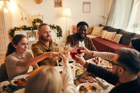 Multi-ethnic group of young people clinking champagne glasses while enjoying Christmas dinner at home, copy space 스톡 콘텐츠