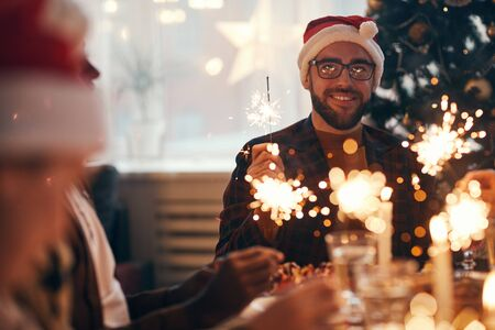 Portrait of cheerful bearded man wearing santa hat while enjoying Christmas celebration dining with friends and family