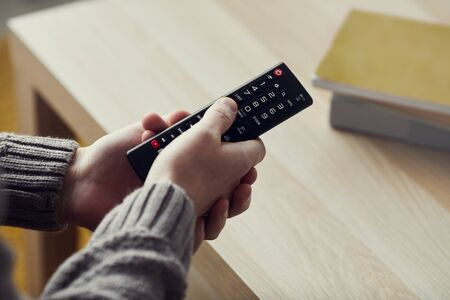 High angle closeup of male hands holding remote control while watching TV at home, copy space Stockfoto