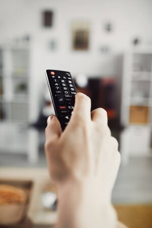 Close up of male hand holding TV remote against big screen television set, copy space