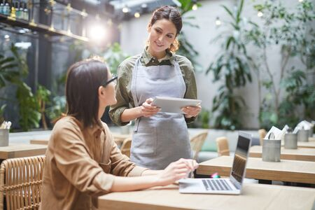 Waist up portrait of young waitress holding digital tablet while taking order of clients at outdoor cafe terrace decorated with plants, copy space