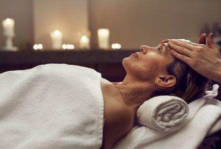 Ritratto di vista laterale di una donna anziana elegante che si gode un massaggio facciale nel lussuoso centro SPA, copia spazio