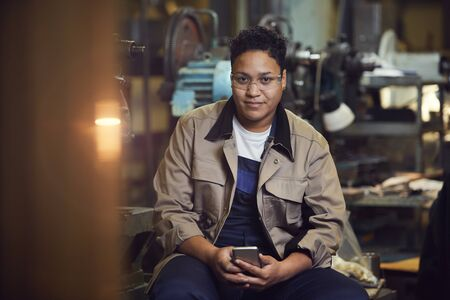 Portrait of contemporary mixed-race woman smiling at camera while posing in factory workshop