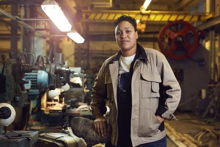 Waist up portrait of contemporary mixed-race woman posing in factory workshop at looking at camera, copy space