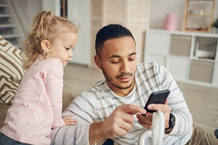 Portrait of contemporary mixed-race man showing smartphone to cute little girl in apartment interior, copy space