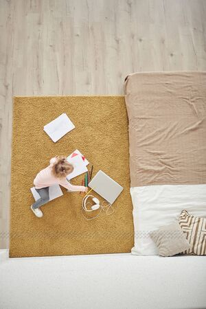 Above view background of little girl playing on floor in cozy bedroom interior, copy space Banco de Imagens - 134734005