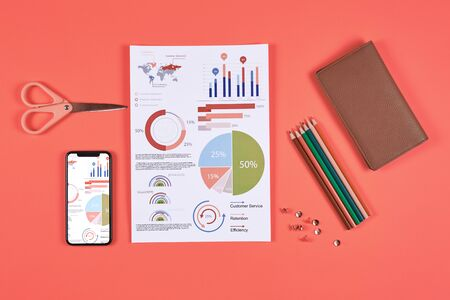 Above view flat lay of business data charts and office supplies over coral background, copy space Banco de Imagens