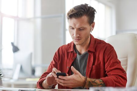 Portrait of contemporary tattooed man using smartphone while working at desk in spacious office, copy space