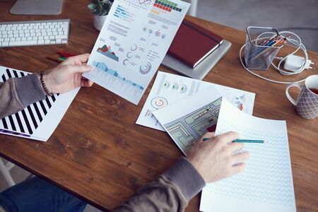 Nahaufnahme eines nicht erkennbaren modernen Geschäftsmannes, der einen Statistikbericht mit farbigen Daten hält, während er am Holzschreibtisch im Büro arbeitet, Kopierraum