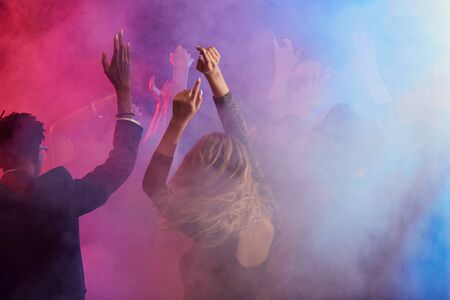 Back view of beautiful young woman dancing and raising hands while enjoying party in smoky nightclub, copy space Stock Photo
