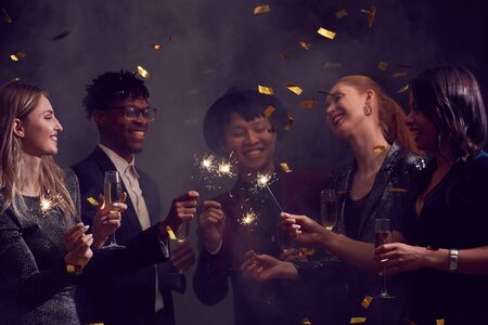 Multi-ethnic group of elegant people enjoying Christmas party in smoky night club with glitter falling overhead, copy space Archivio Fotografico