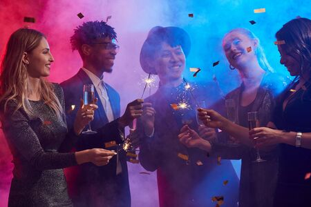 Multi-ethnic group of elegant young people enjoying Christmas party in smoky night club with colored lighting