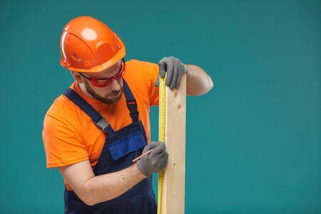 Horizontal studio portrait of carpenter wearing orange and blue uniform sizing wooden plank, turquoise background