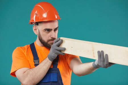 Horizontal studio medium portrait shot of manual worker wearing uniform checking quality of wooden plank