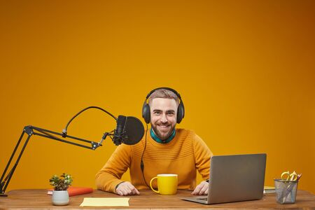 Horizontal studio portrait of young adult man working as radio presenter sitting at table in his workplace looking at camera