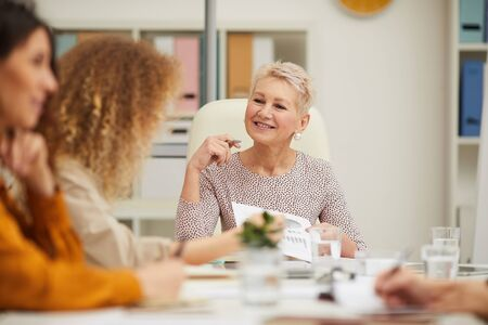Mature Caucasian boss having active discussion with her emplyees at business meeting, horizontal eye level shot Imagens