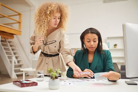 Two ethnically diverse young women coworking on new fashion collection fabric choice in modern office Stock Photo