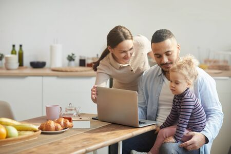 Warm-toned portrait of modern mixed race-family using computer while sitting in cozy kitchen interior with cute little daughter, copy space