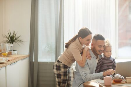 Warm toned portrait of modern mixed race-family using laptop while sitting in cozy kitchen interior with cute little daughter, copy space 写真素材