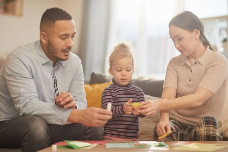 Warm toned portrait of happy mixed-race family playing with cute little girl in cozy home interior 写真素材