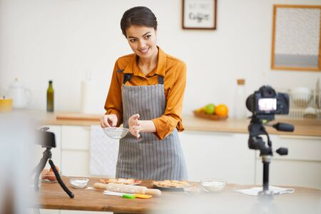Waist up portrait of beautiful young woman looking at camera while filming baking tutorial for video channel, copy space
