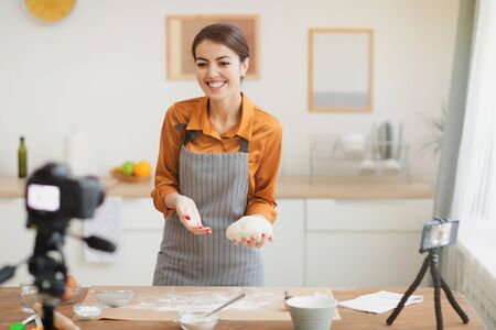 Portrait of beautiful young woman holding fresh batter and smiling at camera while filming baking tutorial for video channel, copy space Stockfoto