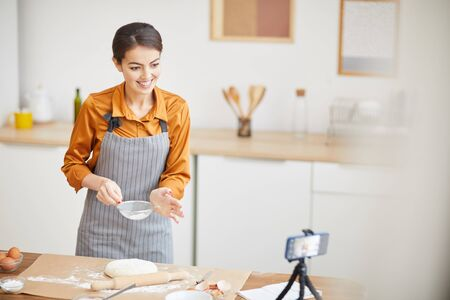 Waist up portrait of beautiful young woman smiling at camera while filming baking tutorial for video channel, copy space
