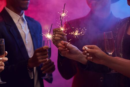 Closeup of young people lighting sparklers while enjoying Christmas party in smoky night club, copy space Archivio Fotografico