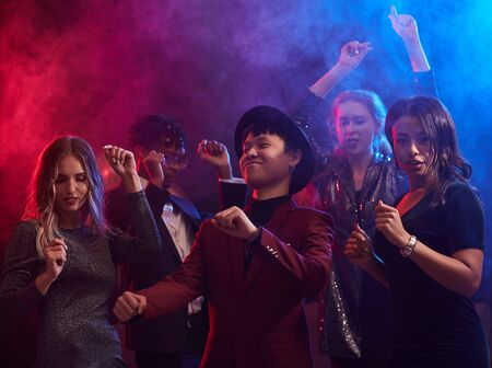 Multi-ethnic group of trendy young people dancing in smoky nightclub, two beautiful women in foreground, copy space Stock Photo
