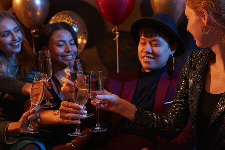Waist up portrait of multi-ethnic group of elegant young people clinking champagne glasses during party in nightclub