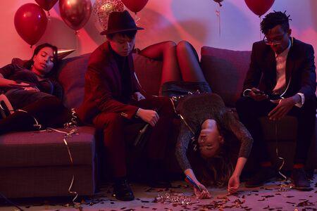 Gruppe betrunkener junger Leute, die nach einer wütenden Party im Nachtclub auf der Couch schlafen, Kopierraum