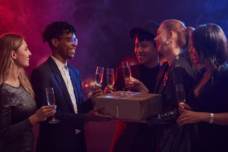 Multi-ethnic group of elegant young people exchanging presents during party in smoky night club Archivio Fotografico