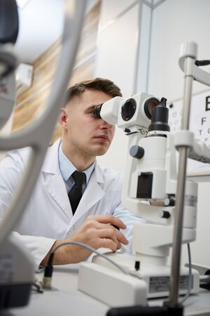 Portrait of male optometrist using refractometer machine while testing vision of unrecognizable patient
