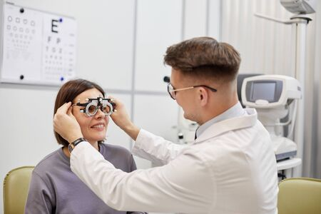 Portrait of young ophthalmologist putting trial frame on smiling female patient during vision check in modern clinic, copy space Foto de archivo
