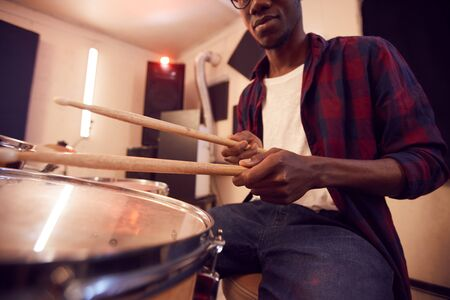Cropped portrait of young African-American man playing drums with contemporary music band during rehearsal or concert in studio, copy space