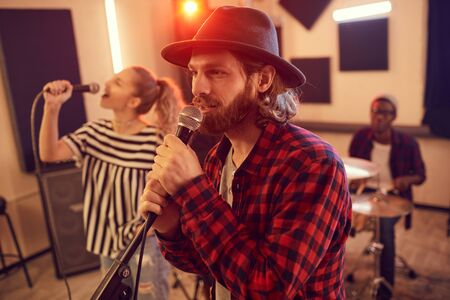 Side view portrait of handsome bearded man singing to microphone during rehearsal or concert with music band, copy space