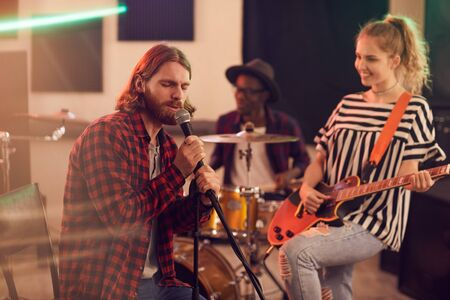 Portrait of bearded man singing to microphone during rehearsal or concert with music band in studio, copy space Imagens